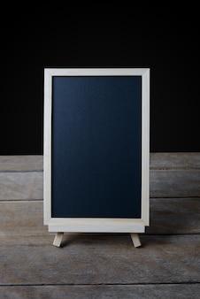 Tableau noir sur le stand sur plancher en bois et fond noir