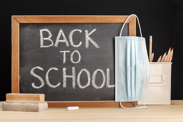 Tableau noir avec le texte écrit de retour à l'école et masque facial accroché au tableau