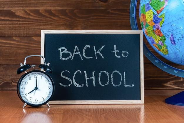 Un tableau noir avec le texte de retour à l'école, un réveil et un globe sur un fond en bois