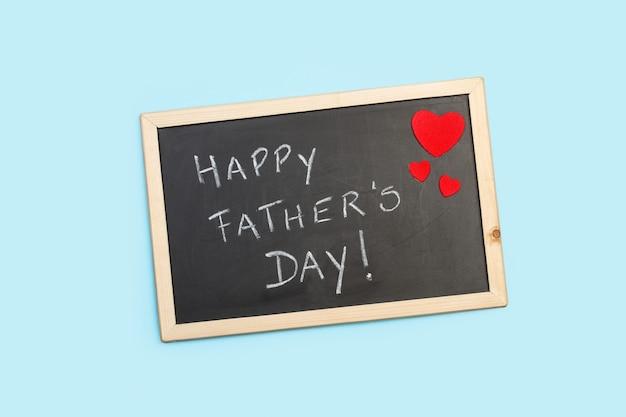 Tableau noir avec voeux de fête des pères sur un fond bleu clair