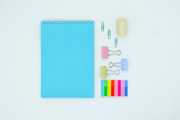 Tableau rouge abstrait avec papeterie. cahier vierge et des ciseaux, des stylos, des stylos. surface horizontale de la vue horizontale supérieure à plat.