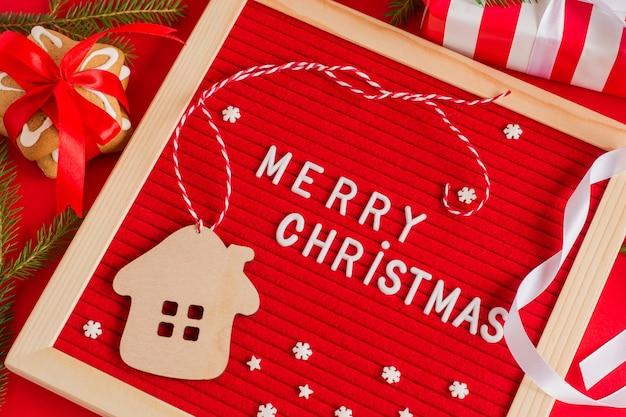 Tableau rouge avec des salutations de joyeux noël décoré de coffrets cadeaux rouges et blancs et de flocons de neige en sucre.