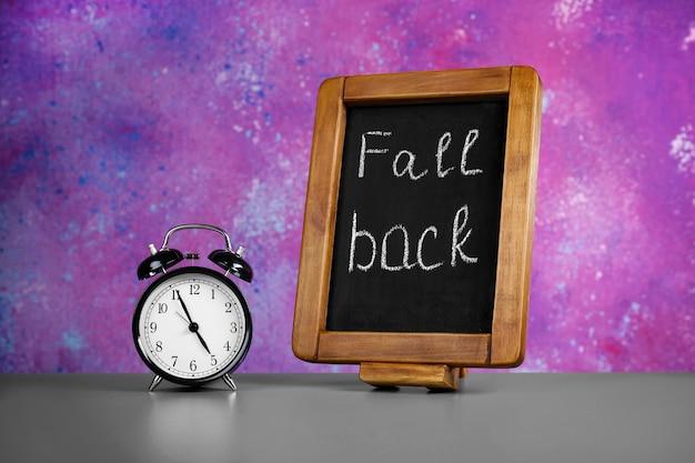 Tableau avec texte fall back et réveil rétro sur table contre mur de couleur