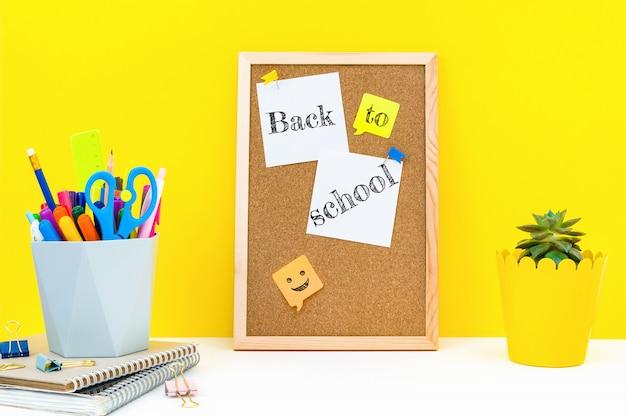 Tableau vertical pour les notes et les mots retour à l'école sur des feuilles autocollantes attachées, des fournitures de bureau et une plante sur la table en classe.