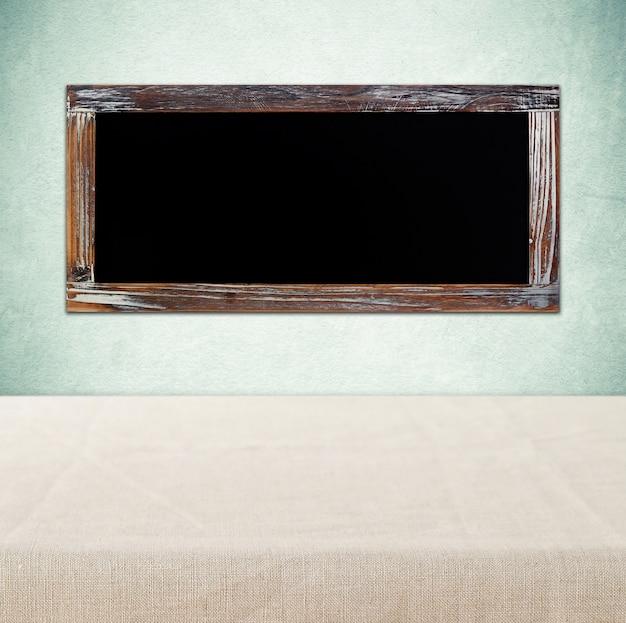 Tableau vide accroché sur le mur vert sur la table vide