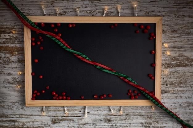 Tableau vide avec bords en bois et petits fruits rouges et lumières