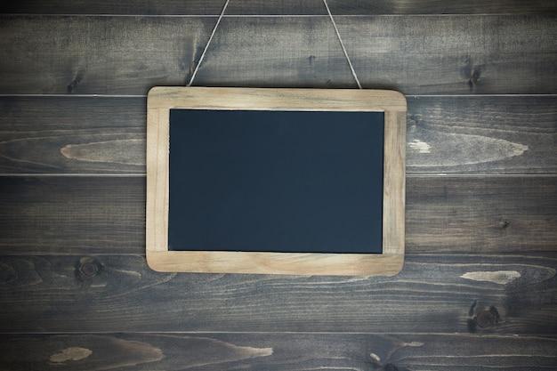 Tableau vide sur la corde attachée à un fond en bois blanc minable