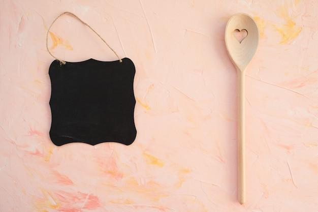 Tableau vide et cuillère en remuant sur fond rose