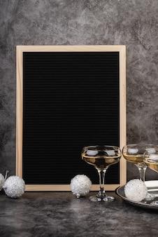 Tableau vide en feutre noir avec des verres de champagne et des décorations du nouvel an