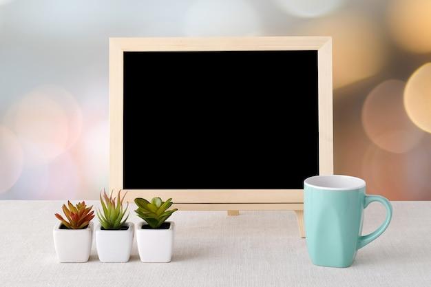 Tableau vide et tasse de café vert debout sur la nappe de sac sur fond de bokeh de flou