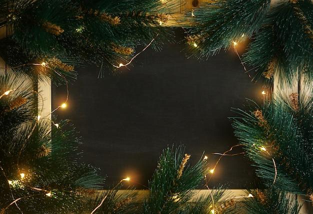 Tableau vide vide entouré d'une branche de sapin et de lumière de noël
