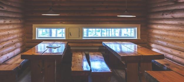 Tables et bancs en bois dans une maison en rondins dans la forêt