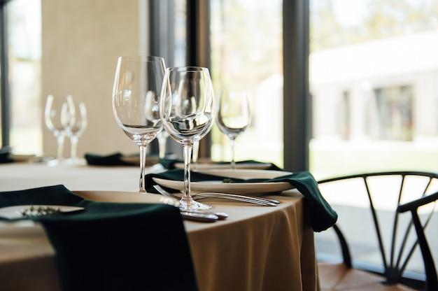 Tables blanches intérieures luxueuses de restaurant luxueux servant des plats et des verres pour des invités