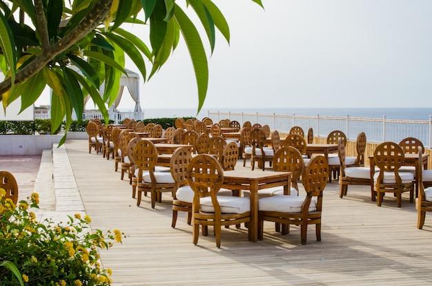 Tables et chaises en bois sur la terrasse du café d'été confortable avec vue sur la mer.
