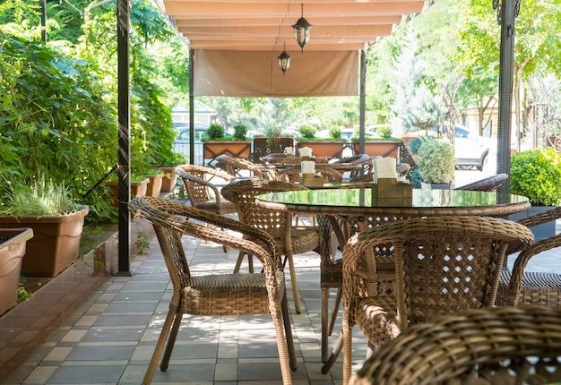 Tables et chaises en osier dans un café d'été en plein air avec des parterres de fleurs