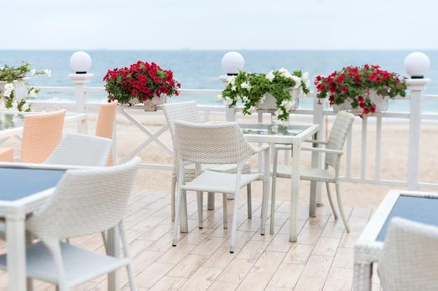Tables et chaises vides d'un restaurant sur une terrasse donnant sur la mer, café avec vue sur la mer.