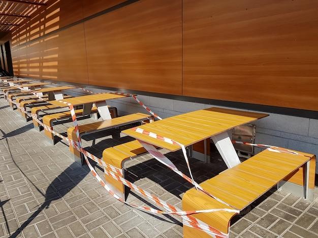 Tables enveloppées de ruban adhésif dans un café en plein air fermé pendant la quarantaine en raison d'un coronavirus