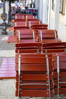 Des tables de rue de café avec des chaises vides attendent les visiteurs en structure rouge.