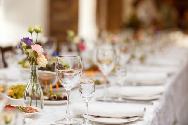 Tables servies avec drap blanc et assiettes vides