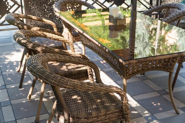 Tables en verre et chaises en osier dans le café d'été en plein air