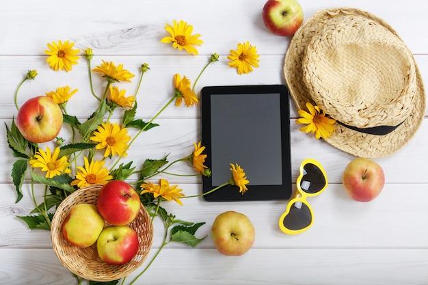 Tablet pc avec des accessoires rustiques dans un fond en bois clair.
