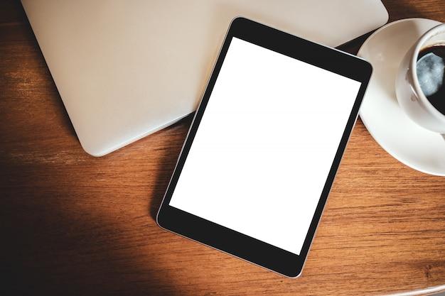 Tablet pc noir avec écran blanc de bureau blanc avec ordinateur portable et tasse de café sur la table en bois