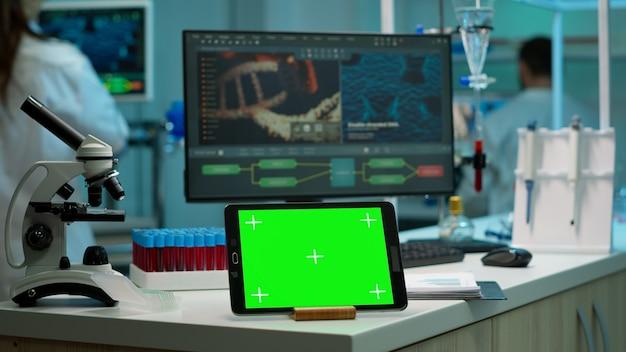 Tablette d'affichage avec écran vert, maquette sur un modèle placé sur un bureau dans un laboratoire scientifique pendant qu'une femme scientifique en recherche médicale analyse l'évolution du virus sur un moniteur numérique effectuant une expérience