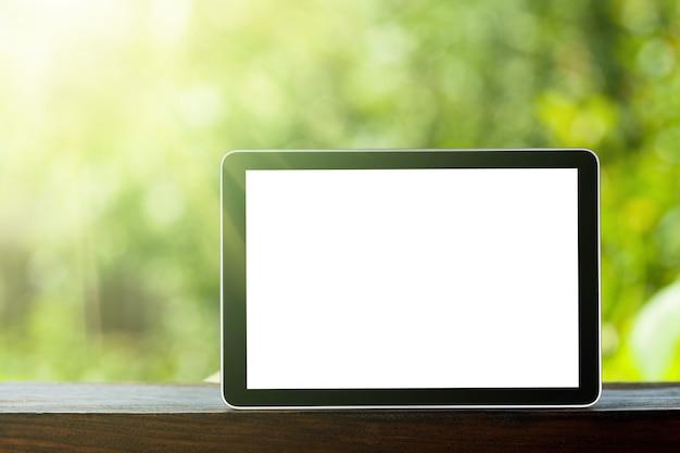 Tablette sur les arrière-plans verts de bokeh. comme ipad
