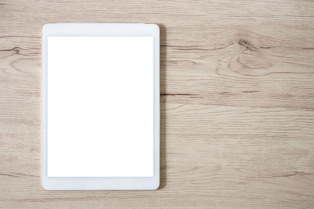 Tablette blanche isolée sur une table en bois