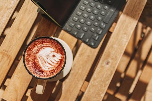 Tablette avec café chaud sur le bureau avec chaud soleil d'été