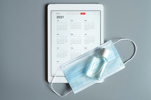 Une tablette avec un calendrier ouvert pour 2021 ans et un masque médical de protection et un désinfectant pour les mains sur un gris