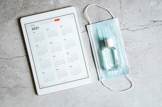 Une tablette avec un calendrier ouvert pour 2021 ans et un masque médical de protection