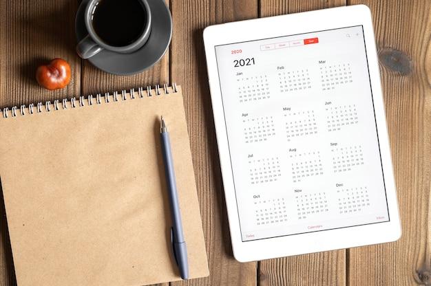 Une tablette avec un calendrier ouvert pour 2021 ans, une tasse de café, des châtaignes et un cahier de papier craft sur un fond de table en bois