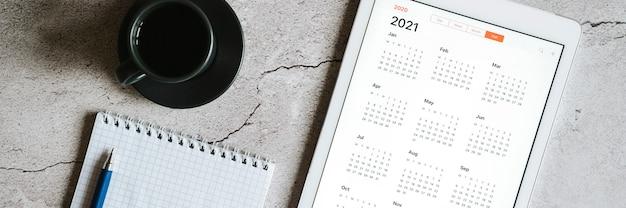 Une tablette avec un calendrier ouvert pour l'année 2021, une tasse de café et un cahier de printemps avec un stylo sur un fond de béton gris. bannière