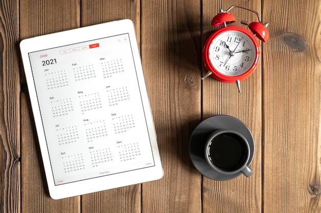 Une tablette avec un calendrier ouvert pour l'année 2021, une tasse de café et un réveil rouge sur un fond de table en bois