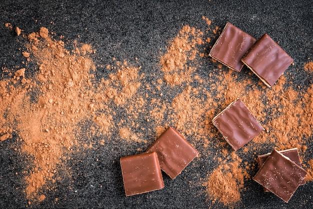Tablette de chocolat au lait, pépites de chocolat et cacao sur fond noir