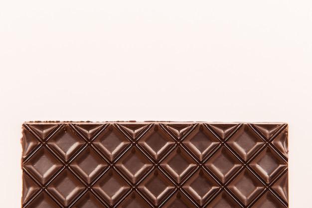 Tablette de chocolat brun sur blanc. espace copie