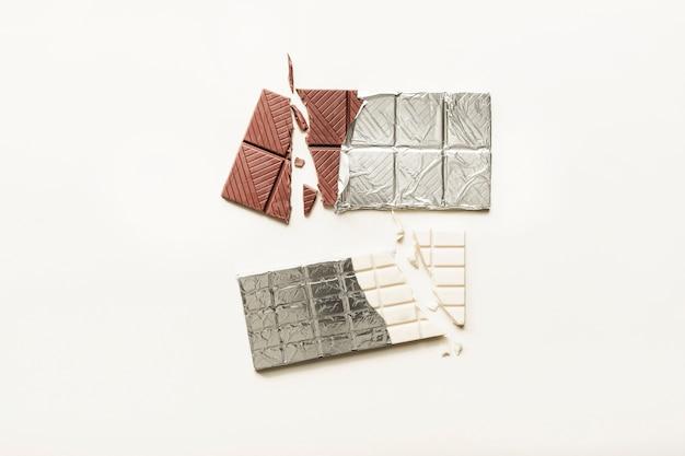 Tablette de chocolat cassée blanche et brune enveloppée dans du papier d'aluminium sur un fond uni