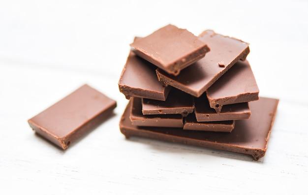 Tablette de chocolat empilée sur le fond de bois blanc pièces de chocolat bonbons dessert sucré et collation