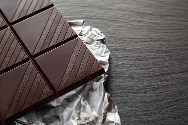 Tablette de chocolat noir avec de grandes cellules sur papier d'aluminium