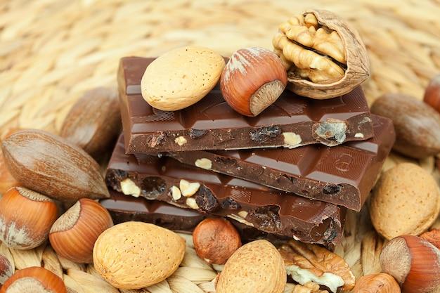 Tablette de chocolat et noix sur un tapis en osier