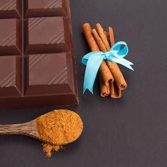Tablette de chocolat, rouleaux de cannelle, cuillère en bois de cannelle