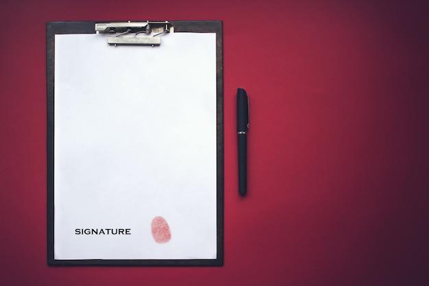 La tablette avec un clip pour le trombone, feuille blanche a4 se trouve avec empreinte digitale au lieu d'une signature sur fond rouge. stock photo avec place vide pour votre texte et votre design.