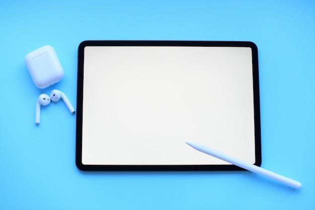 Tablette, avec crayon et air pods sur fond bleu