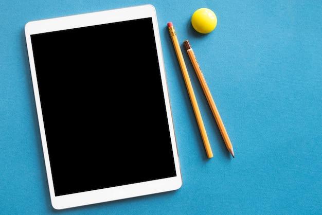 Tablette et crayons sur une surface bleue