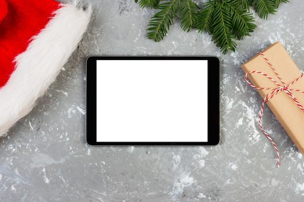 Tablette sur la décoration de noël avec boîte de cadeau et chapeau de santa. vacances du nouvel an