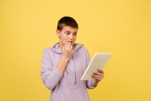 Tablette de défilement peur. portrait de fille caucasienne isolé sur mur jaune avec fond.