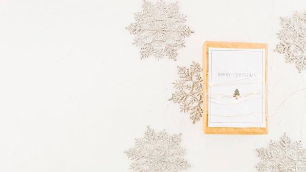 Tablette avec du papier dans les guirlandes lumineuses près de flocons de neige décoratifs