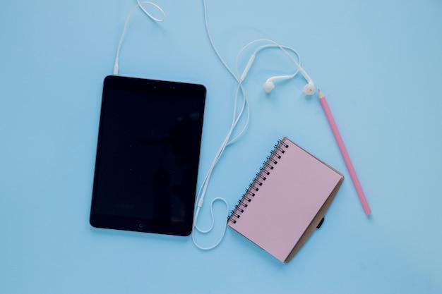 Tablette avec écouteurs près de bloc-notes et un crayon