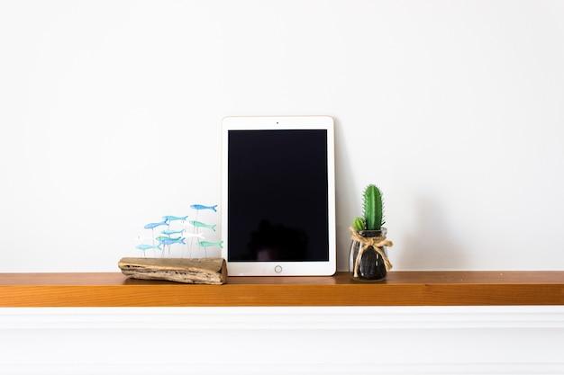 Tablette avec écran blanc sur bois avec cactus